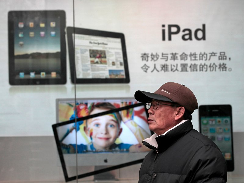 © AP/Eugene Hoshiko, A man stands near Apple's iPad advertisement in Shanghai, China.