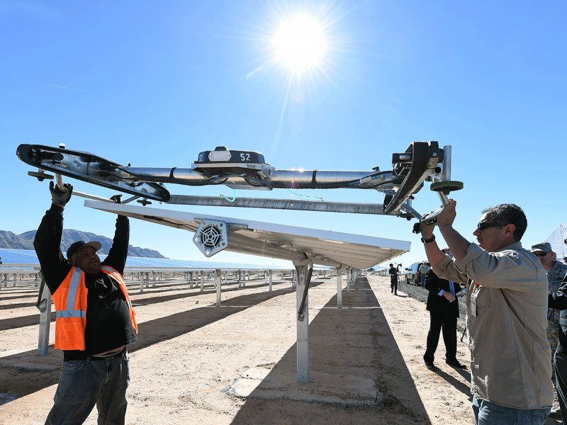 © Ethan Miller / Getty, Workers install a panel washing robot on the 28-megawatt solar farm at Nellis Air Force Base in Las Vegas, Nevada on February 16, 2016. In 2007, former President George W. Bush signed a law requiring the Pentagon get at least a quarter of its electricity from renewables by 2025.