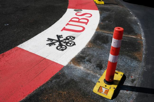 © Bloomberg. Branding for the Swiss bank, UBS Group AG, a sponsor of the Monaco Grand Prix is seen painted onto the road surface of the Formula One Grand Prix Circuit in Monte Carlo, Monaco, on Tuesday, May 29, 2018. The Monaco Grand Prix is the premier race on the Formula 1 calendar and has been held in one form or another since 1929 and in modern form since 1950.