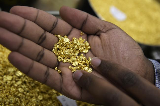 © Bloomberg. An employee holds a handful of gold granules at the Perth Mint Refinery, operated by Gold Corp., in Perth, Australia, on Thursday, Aug. 9, 2018. Demand for coins and minted bars was a little sluggish over the past year as Donald Trump's earlier win in the presidential poll prompted investors to divert funds into stocks, bonds and property, said Perth Mint's Chief Executive Officer Richard Hayes on Aug. 8. Photographer: Carla Gottgens/Bloomberg