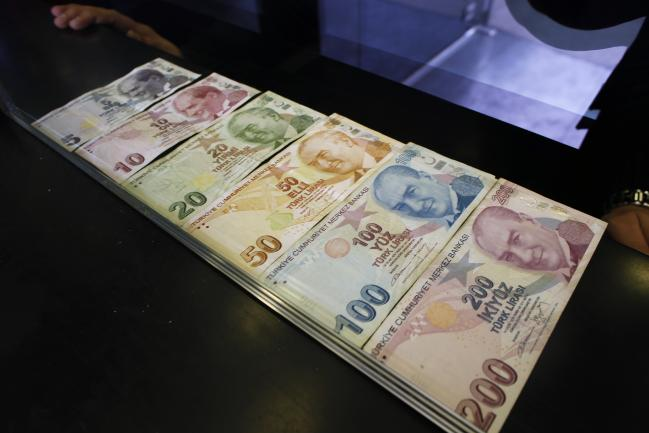 © Bloomberg. Turkish lira banknotes sit in this arranged photograph at a currency exchange in Istanbul, Turkey, on Friday, March 16, 2018. Photographer: Kostas Tsironis/Bloomberg
