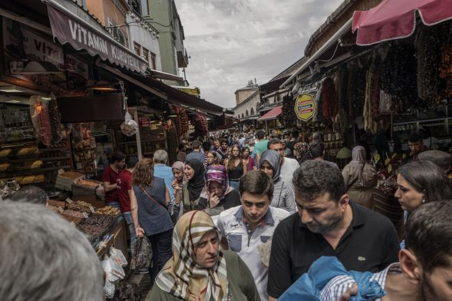 © Bloomberg. Crowds of people move past store fronts at the Eminonu market in Istanbul, Turkey, on Friday, Aug. 17, 2018. Turkish President Recep Tayyip Erdogan argued citizens should buy gold, then he said sell. Add dramatic swings in the lira, and the country's traders are now enthusiastically doing both.