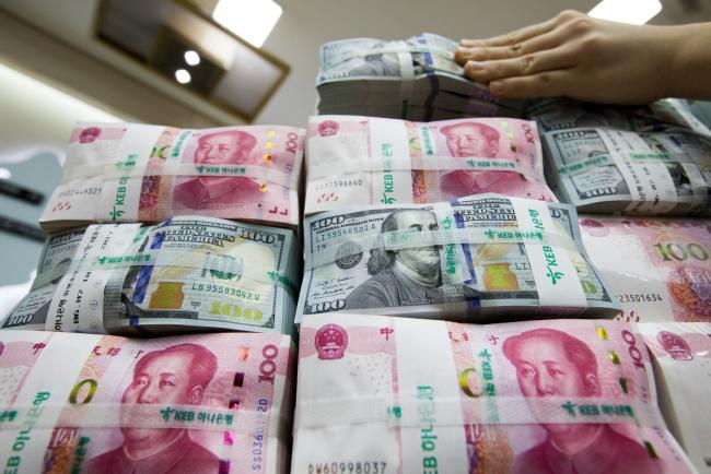 © Bloomberg. An employee arranges genuine bundles of U.S. one-hundred dollar banknotes and Chinese one-hundred yuan in an arranged photograph at the Counterfeit Notes Response Center of KEB Hana Bank in Seoul, South Korea, on Monday, Aug. 14, 2017. China's factory output and investment slowed somewhat in July, according to data released today, yet the yuan appeared not to take the data as negative, if in fact it's paying attention to it at all. Photographer: SeongJoon Cho/Bloomberg