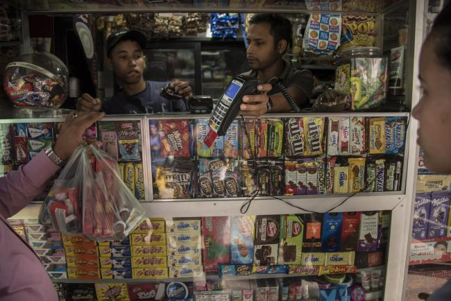 © Bloomberg. A customer pays for candy with a credit card at a stand in the Chacao district of Caracas, Venezuela, on Wednesday, Dec. 6, 2017. Venezuelan President Nicolas Maduro announced the nation would create its own cryptocurrency, the