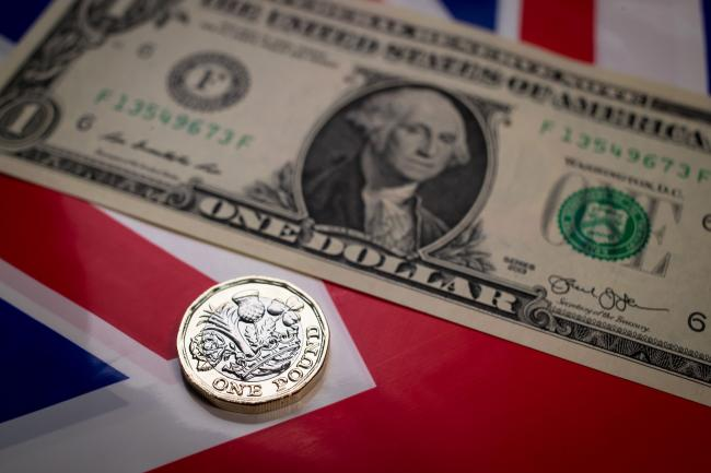 © Bloomberg. BATH, ENGLAND - APRIL 04: In this photo illustration the new 1 pound coin is seen alongside US dollar bills on April 4, 2017 in Bath, England. Currency experts have warned that as the uncertainty surrounding Brexit continues, the value of the British pound, which has remained depressed against the US dollar and the euro since the UK voted to leave in the EU referendum, is likely to fluctuate. (Photo by Matt Cardy/Getty Images) Photographer: Matt Cardy/Getty Images Europe