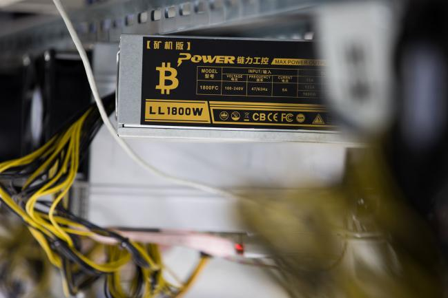 © Bloomberg. The bitcoin symbol is displayed on a power supply unit at a cryptocurrency mining facility in Incheon, South Korea, on Friday, Dec. 15, 2017. Hedge funds are pulling out of gold bets as more exciting moves in equities and cryptocurrencies make safe-haven investments look boring.