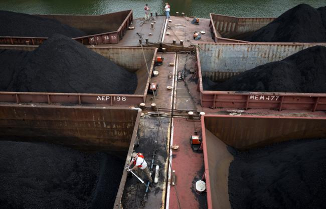 © Bloomberg. Workers on the American Electric Power Co.'s AEP Leader towboat tighten down lines connecting 15 barges together holding 30,000 tons of coal before making their way down the Ohio River in West Virginia, U.S., on Tuesday, Oct. 23, 2012.  Photographer: Ty Wright/Bloomberg
