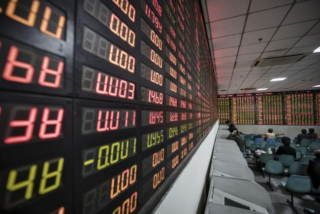 © Bloomberg. Investors stand at trading terminals in front of an electronic stock board at a securities brokerage in Shanghai, China, on Wednesday, Nov. 9, 2016. Global markets were thrown into disarray as early results from the U.S. election raised the possibility that Donald Trump may prevail over Hillary Clinton in the race for the presidency, shocking traders who had focused on polls in recent days showing the opposite. Photographer: Qilai Shen/Bloomberg