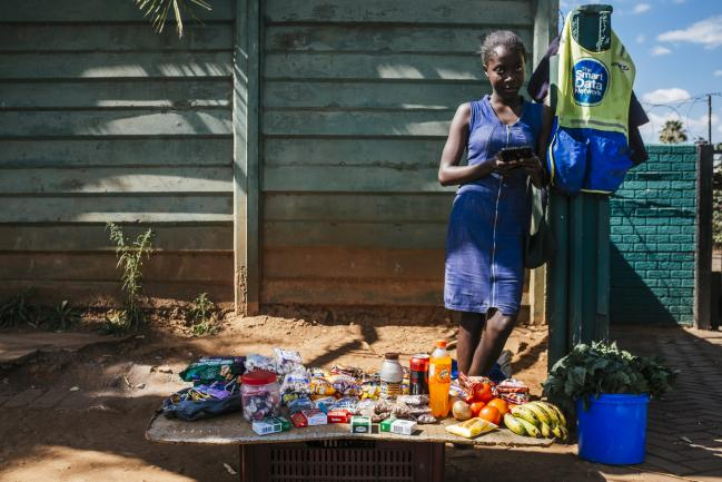 © Bloomberg. A street vendor selling fresh fruit, vegetables and packaged food looks up from her mobile telephone in Harare, Zimbabwe, on Tuesday, July 31, 2018. Photographer: Waldo Swiegers/Bloomberg