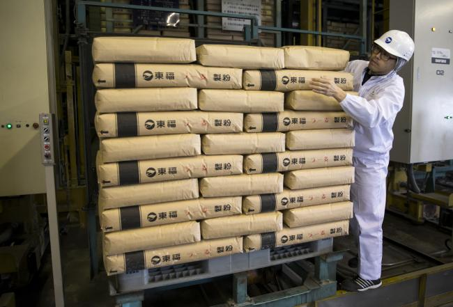 © Bloomberg. A Tofuku Flour Mills Co. employee moves a bag of flour for ramen noodles at the company's warehouse in Dazaifu, Fukuoka, Japan, on Dec. 21, 2017. Fukuoka, on Japan's southern island of Kyushu, is expanding production of a locally-developed variety of grain known as Ra-Mugi that's designed to be perfect for tonkotsu ramen: a dish of cloudy white pork broth, with noodles and slices of pork that originates in the region.