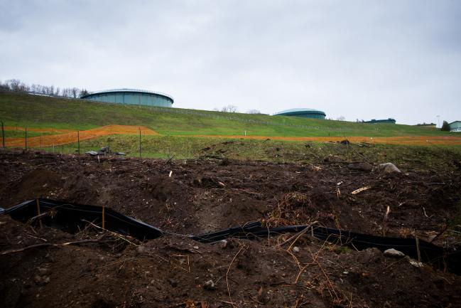 © Bloomberg. Oil tanks stand near the Kinder Morgan Inc. Trans Mountain pipeline expansion site in Burnaby, British Columbia, Canada, on Wednesday, April 11, 2018. Alberta, the landlocked Canadian province that's home to the oil sands, would be willing to buy out Kinder Morgan's Trans Mountain pipeline if that's the only way to salvage the critical export route, Premier Rachel Notley said.