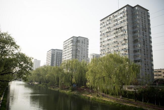 © Bloomberg. Residential buildings and willow trees stand along a canal in the Yonghegong area of Beijing, China, on Monday, April 16, 2018. New home prices in Beijing and Shanghai have jump more than 25 percent over the last two years. Photographer: Giulia Marchi/Bloomberg