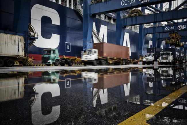 © Bloomberg. Trucks are reflected in a puddle as they wait in line to unload their containers onto CMA CGM SA's Benjamin Franklin container ship docked at the Guangzhou Nansha Container Port in Guangzhou, China, on Monday, Feb. 1, 2016. Photographer: Qilai Shen/Bloomberg