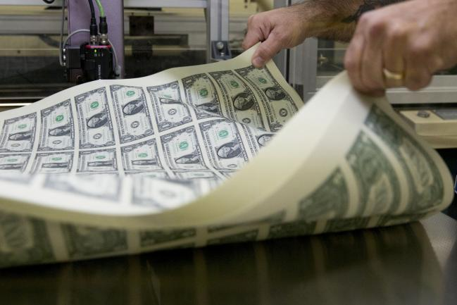 © Bloomberg. A pressman aerates a stack of 2017 50 subject uncut sheet of $1 dollar notes bearing the name of U.S. Treasury Secretary Steven Mnuchin at the U.S. Bureau of Engraving and Printing in Washington, D.C., U.S., on Wednesday, Nov. 15, 2017. A change in the Senate tax-overhaul plan that would expand a temporary income-tax break for partnerships, limited liability companies and other so-called