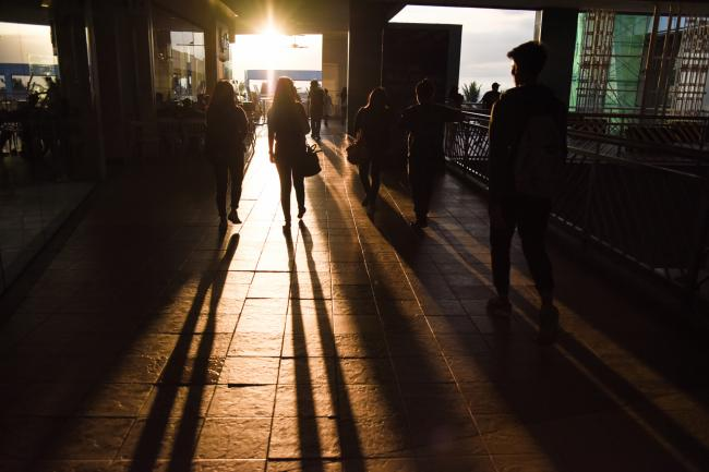 © Bloomberg. Pedestrians cast shadows on a walkway to the SM by the Bay amusement park in the SM Mall of Asia complex, operated by SM Prime Holdings Inc., at sunset in Pasay City, Metro Manila, the Philippines, on Tuesday, March 6, 2018. SM Prime became the Philippines' most valuable property company after building 68 malls throughout the nation, but it may just be embarking on its most important project to date: an e-commerce platform to fight off the growing challenge from online retailers. Photographer: Carlo Gabuco/Bloomberg