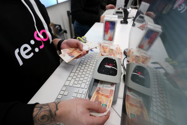 © Bloomberg. An employee feeds ruble banknotes through a validation machine in payment for iPhone X smartphones at a re:Store Apple Inc. retailer on the first day of sale in Moscow, Russia, on Friday, Nov. 3, 2017. Supported by resurgent iPad and Mac sales, the 10-year anniversary iPhone will help push revenue to a record high of $84 billion to $87 billion in the quarter ending in late December, Apple said in a statement. Photographer: Andrey Rudakov/Bloomberg