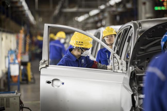 ©彭博社。 员工在上汽通用五菱汽车有限公司宝骏基地工厂的焊接车间检查车辆,该工厂是上汽集团,通用汽车公司和柳州五菱汽车工业有限公司在中国广西柳州的合资企业, 2018年5月23日,星期三,通用汽车及其合作伙伴在中国销售了400万辆汽车,比在美国销售的汽车制造商多出约100万辆。摄影师:Qilai Shen / Bloomberg