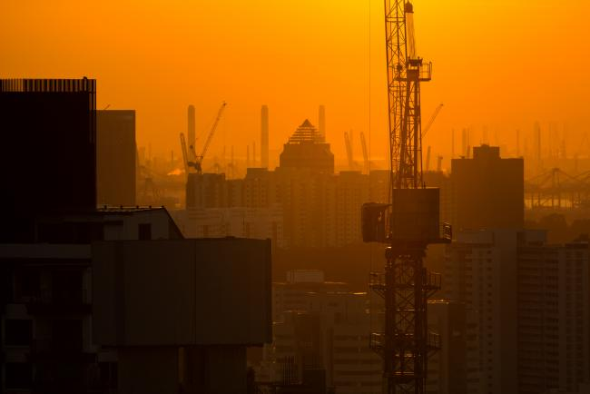© Bloomberg. A crane standing at the construction site is silhouetted at dusk in Singapore, on Thursday, Sept. 15, 2016. Singapore is currently mired in its most prolonged housing slump on record. Home prices in the city-state fell for the 11th straight quarter in the three months ending June 30, posting the longest losing streak since records started in 1975. Photographer: SeongJoon Cho/Bloomberg