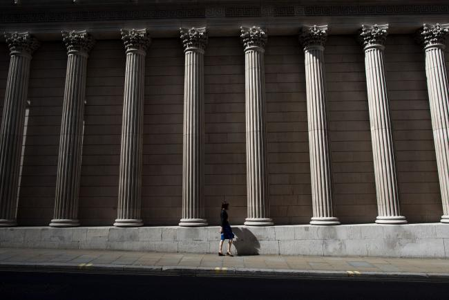 © Bloomberg. A pedestrian walks past the Bank of England in the City of London, U.K., on Monday July 31, 2017. Consumer credit growth slowed in June after the Bank of England officials took action to limit some areas of risk of borrowing.