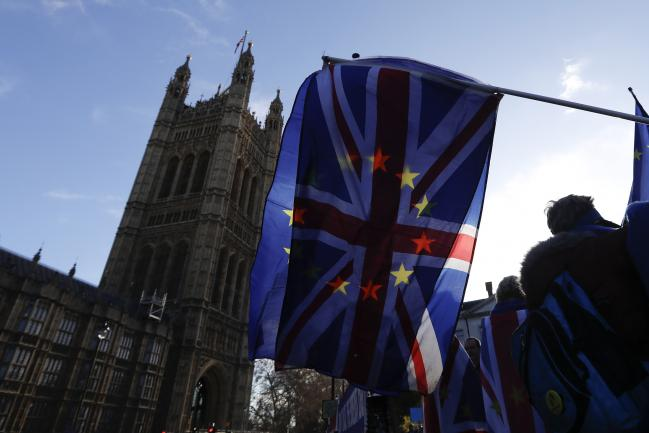 © Bloomberg. A British Union flag, also known as a Union Jack, flies beside a European Union (EU) flag during ongoing pro and anti Brexit protests outside the Houses of Parliament in London, U.K., on Tuesday, Jan. 22, 2019. The U.K.'s main opposition party is backing a plan that could open the door to a second European Union referendum, bringing the possibility of stopping Brexit a step closer. Photographer: Luke MacGregor/Bloomberg