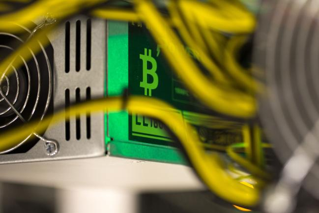 © Bloomberg. A bitcoin logo sits on a LL 1800W power unit supplying cryptocurrency mining machines at the SberBit mining 'hotel' in Moscow, Russia, on Saturday, Dec. 9, 2017. Futureson the worlds most popular cryptocurrency surged as much as 26 percent in their debut session on Cboe Global Markets Inc.'s exchange, triggering two temporary trading halts designed to calm the market.