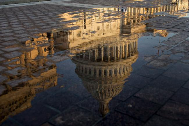 © Bloomberg. The U.S. Capitol building is reflected in a puddle at sunrise in Washington, D.C., U.S., on Wednesday, July 19, 2017. The Senate early next week will consider the motion to proceed to legislation to repeal Obamacare without finding a replacement for two years after a setback for Republicans' efforts this week to repeal and replace the bill. Senate Majority Leader McConnell said he's scheduling the vote at the request of President Trump and Vice President Pence. Photographer: Andrew Harrer/Bloomberg