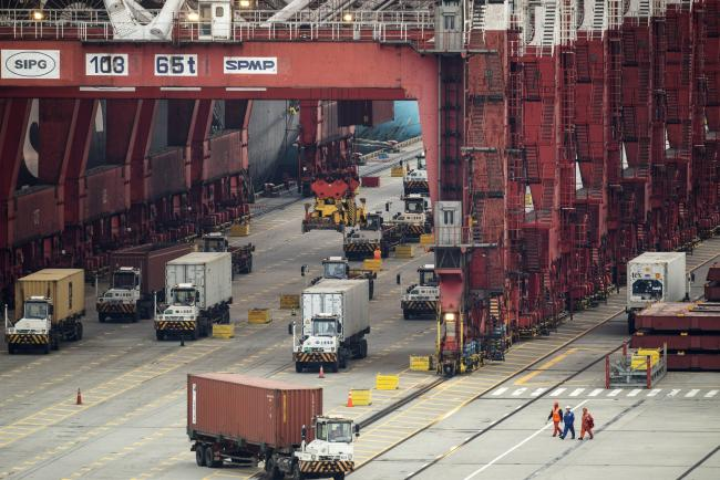 © Bloomberg. Vehicles travel under gantry cranes at the Yangshan Deepwater Port, operated by Shanghai International Port Group Co. (SIPG), in Shanghai, China, on Friday, May 10, 2019.  Photographer: Qilai Shen/Bloomberg