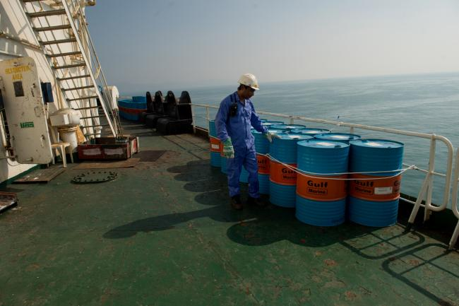 © Bloomberg. A crew man secures Gulf Marine oil drums on the deck of oil tanker 'Devon' as it prepares to transport crude oil from Kharq Island to India in Bandar Abbas, Iran. Photographer: Ali Mohammadi/Bloomberg
