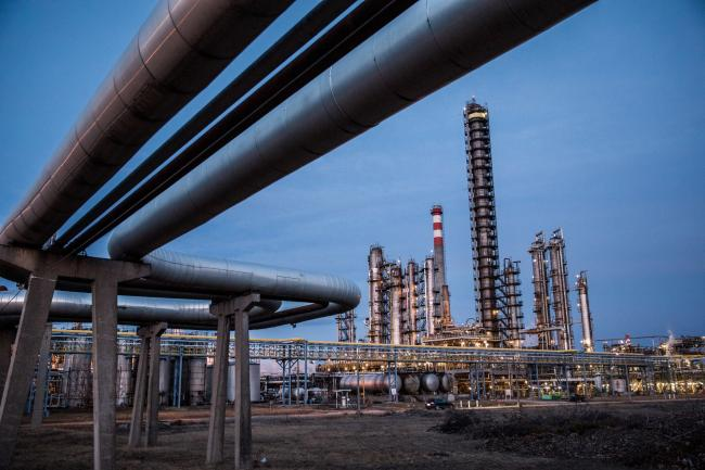 © Bloomberg. Oil cracking towers stand in the Duna oil refinery, operated by MOL Hungarian Oil & Gas Plc, in Szazhalombatta, Hungary, on Monday, Feb. 13, 2019. Oil traded near a three-month high as output curbs by OPEC tightened global supply while trade talks between the U.S. and China lifted financial markets.