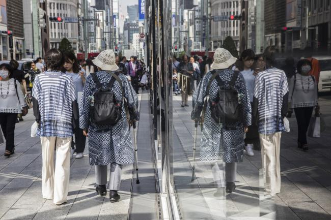 © Bloomberg. Pedestrians are reflected in windows at the Ginza district of Tokyo, Japan, on Friday, May 25, 2018.  Photographer: Shiho Fukada/Bloomberg
