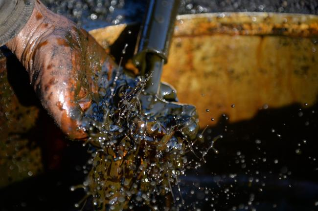 © Bloomberg. Extracted crude oil splashes on a worker's hand as it's being pours from a pipe in the village of Wonocolo, East Java, Indonesia.