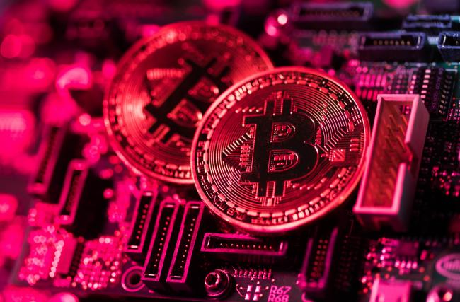 © Bloomberg. Two coins representing Bitcoin cryptocurrency sit on a computer circuit board in this arranged photograph in London, U.K., on Tuesday, Feb. 6, 2018. Cryptocurrencies tracked by Coinmarketcap.com have lost more than $500 billion of market value since early January as governments clamped down, credit-card issuers halted purchases and investors grew increasingly concerned that last year's meteoric rise in digital assets was unjustified.