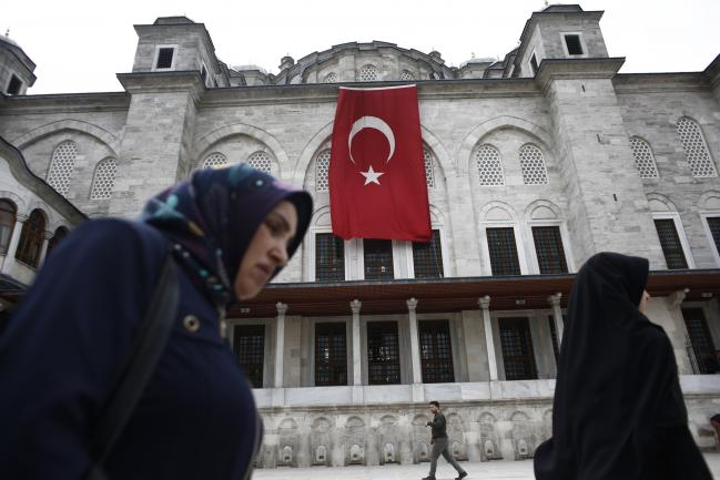 © Bloomberg. Pedestrians pass a Turkish flag hanging from the Fatih Mosque ahead of a demonstration against the relocation of the U.S. embassy to Jerusalem in Istanbul, Turkey, on Friday, May 11, 2018. No major power recognized Israeli sovereignty in Jerusalem until U.S. President Donald Trump did so on Dec. 6.