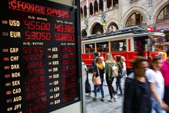 © Bloomberg. Pedestrians pass a digital sign advertising the latest rates for Turkish lira in the window of a currency exchange bureau in Istanbul, Turkey, on Monday, June 25, 2018. The gains in Turkey's lira that followed Recep Tayyip Erdogan'selection victory fizzled out as investors worried that the president's sweeping new powers may stymie efforts to rein in inflation and the widening current-account deficit. Photographer: Kostas Tsironis/Bloomberg