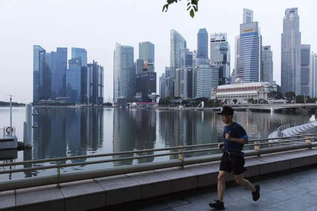 © Bloomberg. A man runs along a promenade past commercial buildings standing in the central business district in Singapore, on Friday, Feb. 16, 2018. Singapore's dollar is little changed near a three-week high amid thin trading with many Asian markets closed for Lunar New Year holidays. The central bank will announce the amount of 30-year bonds to be auctioned next week in the only planned sale of this tenor in 2018.