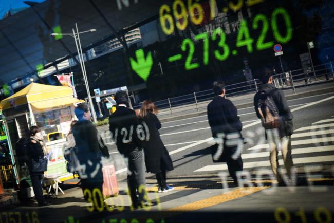 © Bloomberg. Pedestrians are reflected in an electronic stock board outside a securities firm in Tokyo, Japan, on Tuesday, Feb. 6, 2018. Japan's broad Topix index and blue-chip Nikkei 225 Stock Average were poised to enter a correction as the nation's shares headed for the biggest decline since June 2016, following U.S. peers lower amid rising concern that inflation will force interest rates higher.