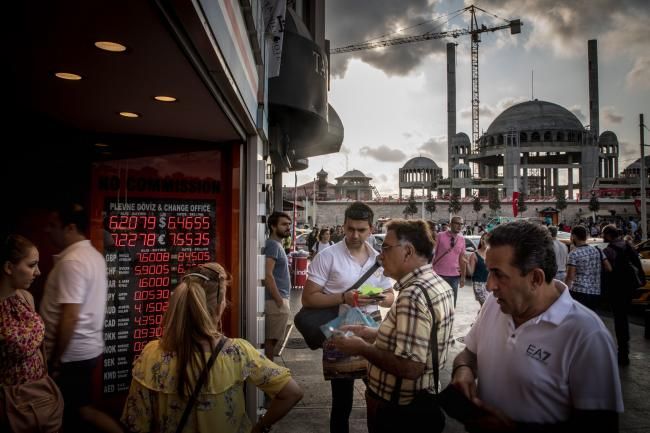 © Bloomberg. ISTANBUL, TURKEY - AUGUST 29: People wait to change money at a currency exchange office in front of the underconstruction, Taksim Square Mosque on August 29, 2018 in Istanbul, Turkey. Turkey's lira extended its slump to a third day to 6.45 against the dollar after the central bank announced it would alter Turkish banks borrowing limits on overnight transactions, the move failed to reassure investors and combined with the decision by ratings agency Moody's to downgrade the credit rating of twenty Turkish financial institutions saw the lira continue to slide. (Photo by Chris McGrath/Getty Images)