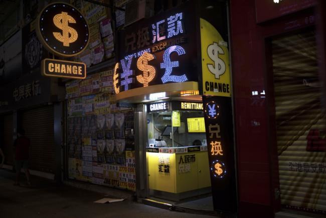 © Bloomberg. Currency symbols are illuminated at a currency exchange store at night in the Mong Kok district of Hong Kong, China.