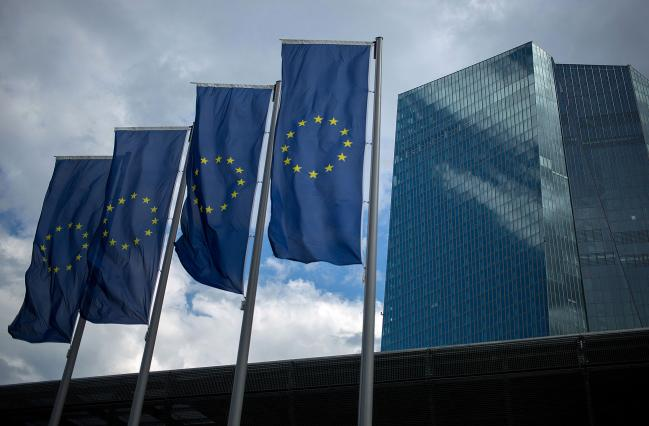 © Bloomberg. The stars of the European Union (EU) sit on banners flying outside the European Central Bank (ECB) headquarters stands in Frankfurt, Germany, on Thursday, July 20, 2017. Frankfurt has emerged as a winner of the Brexit vote, with Standard Chartered Plc, Nomura Holdings Inc., Sumitomo Mitsui Financial Group Inc. and Daiwa Securities Group Inc. picking the city as their EU hub in recent weeks.