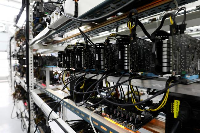 © Bloomberg. Circuit boards and computer equipment sit on shelves at a cryptocurrency mining facility in Incheon, South Korea, on Friday, Dec. 15, 2017. Hedge funds are pulling out of gold bets as more exciting moves in equities and cryptocurrencies make safe-haven investments look boring.