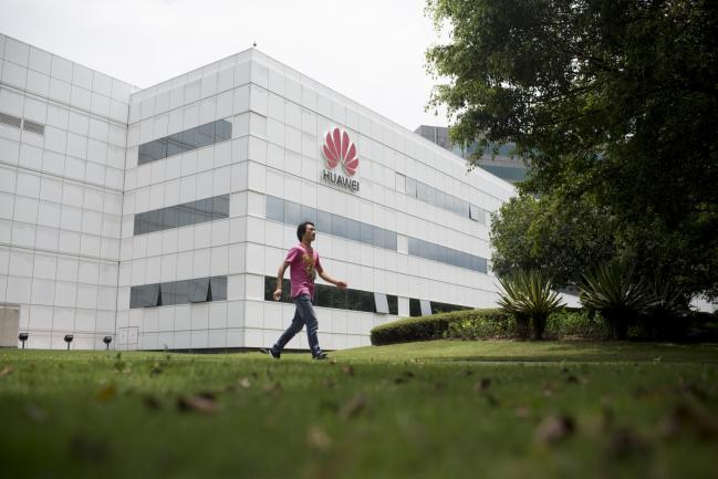 © Bloomberg. An employee walks past a building at the Huawei Technologies Co. campus in the Longgang district of Shenzhen, China, on Wednesday, Aug. 6, 2014.  Photographer: Brent Lewin/Bloomberg