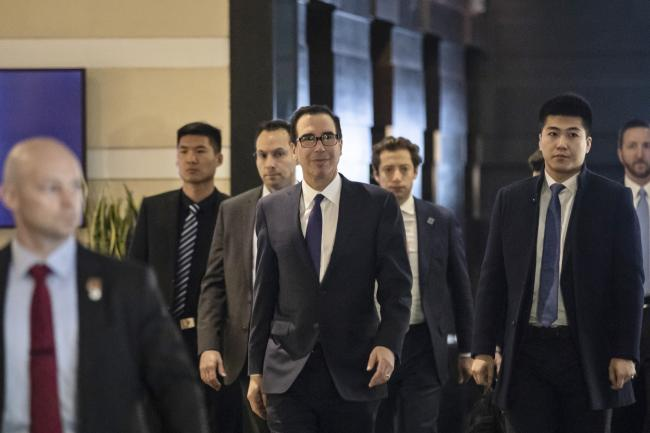 © Bloomberg. Steven Mnuchin, U.S. Treasury secretary, center, leaves a hotel in Beijing, China, on Thursday, Feb. 14, 2019. U.S. President Donald Trump said talks to resolve the trade war with China are making good progress, as face-to-face negotiations continue today in Beijing. Photographer: Qilai Shen/Bloomberg