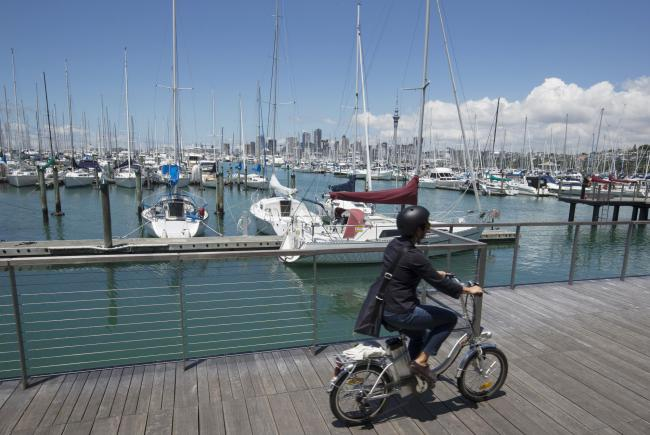 © Bloomberg. A woman rides a bicycle past yachts docked at a marina in Auckland, New Zealand, on Friday, Dec. 9, 2016.  Photographer: Brendon O'Hagan/Bloomberg