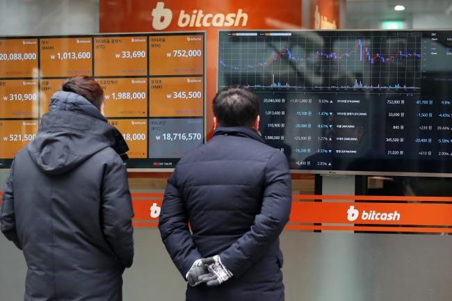 © Bloomberg. Pedestrian look at monitor showing the prices of virtual currencies at the Bithumb exchange office in Seoul, South Korea, on Friday, Dec. 15, 2017.