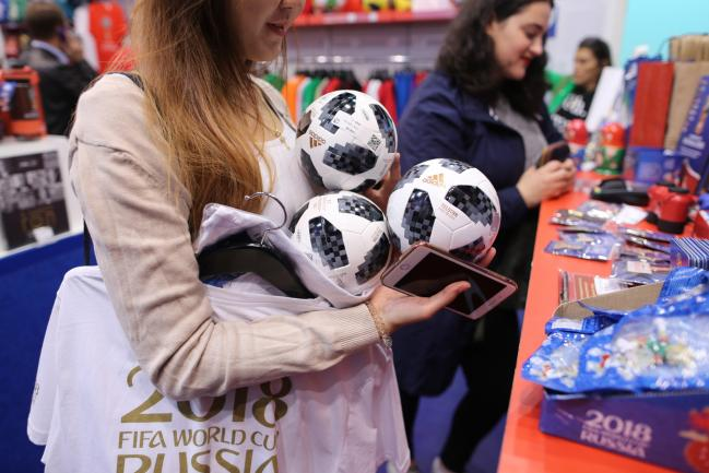 © Bloomberg. A customer selects three replica mini 'Telstar' match balls to purchase inside an official World Cup merchandise store in Moscow, Russia, on Saturday, June 9, 2018.  Photographer: Andrey Rudakov/Bloomberg