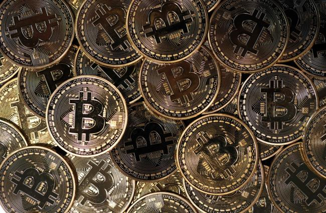 © Bloomberg. A collection of bitcoin tokens sit in this arranged photograph in London, U.K., on Wednesday, Jan. 4, 2017. The electronic coin that trades and is regulated like oil and gold surged 79 percent since the start of 2016 to $778, its highest level since early 2014.
