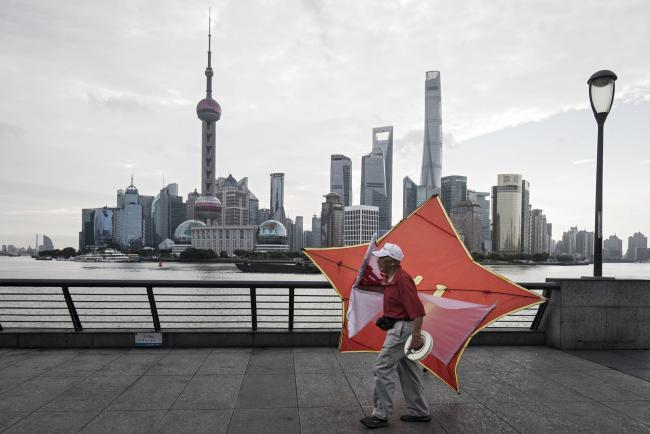 © Bloomberg. A man carries a kite along the bund as the Lujiazui Financial District stands in the background in Shanghai, China, on Monday, Sept. 4, 2017. The Chinese central bank's tight leash on liquidity is straining the bond market, with the benchmark sovereign yield climbing to near the highest level since April 2015. Photographer: Qilai Shen/Bloomberg