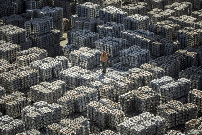 � Bloomberg. A worker stands on bundles of aluminum ingots at a China National Materials Storage and Transportation Corp. stockyard in Wuxi, China, on Thursday, Aug. 23, 2018. The U.S. and China imposed fresh tariffs on each other's goods in the middle of trade talks aimed at averting the worsening conflict between the world's two biggest economies.