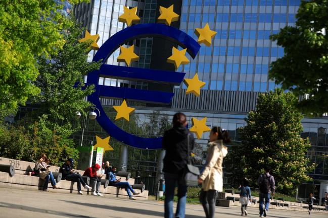© Bloomberg. Visitors look at the euro sign sculpture as it stands near the former European Central Bank (ECB) headquarters in Frankfurt, Germany, on Wednesday, April 25, 2018.  Photographer: Krisztian Bocsi/Bloomberg