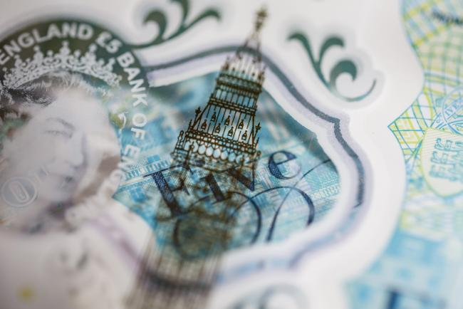 © Bloomberg. The Elizabeth Tower, also known as Big Ben, and a portrait of Queen Elizabeth II are seen on a British five pound banknote, in this arranged photograph in London, U.K.